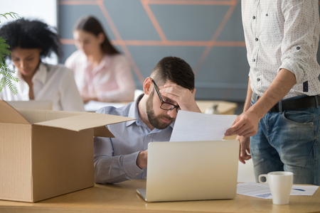 Frustrated upset male employee receiving unfair dismissal notice getting fired from job at workplace, depressed stressed office worker about to pack box on last working day being laid off concept Banque d'images - 100854936