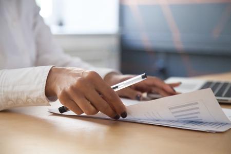 La donna di affari dell'afroamericano che analizza le statistiche del progetto si traduce in un rapporto che lavora con documenti grafici e laptop in ufficio, pianificazione strategica e concetto di analisi dei dati finanziari, vista ravvicinata