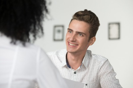 Smiling interested male hr manager interviewing applicant, professional friendly recruiter makes good first impression of job seeker, happy millennial businessman looking at female partner at meeting