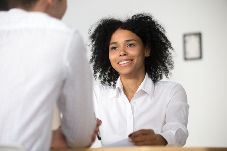 Smiling african female hr employer interviewing male job applicant asking questions, black recruiter attentively listening to seeker, good first impression, human resources management concept Reklamní fotografie - 100856409