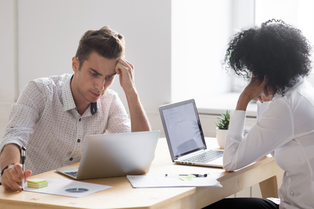 Frustrated stressed african and caucasian colleagues shocked about business failure or bad internet news, sad worried diverse project team partners solving online problem upset by company bankruptcy