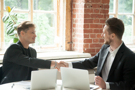 Two male businessmen shaking hands after reaching agreement after successful negotiations on work issues in modern loft office. Horizontal shot, selective focus . Concept of acquisition and partnership