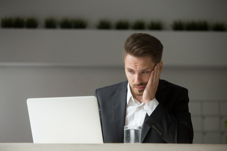 Frustrated and sad businessman hopelessly looking at laptop screen reading bad news of financial breakdown of his company. Concept of business collapse, bankruptcy and crisis
