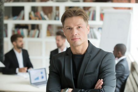 Serious corporate worker looking at camera, company associates discussing business behind. Portrait of confident business man posing for company advertising in office. Concept of teamwork, leadership.