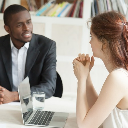 African American and Caucasian managers communicating at office table. Black man listening with attention to colleague talking at company meeting. Concept of diversity, cooperation, human resources