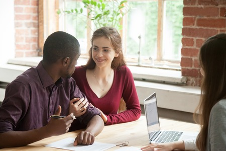 Happy young multiracial couple looking at each other before signing contract of house purchase from female real estate agent. Caucasian wife supports black husband. Concept of new beginning