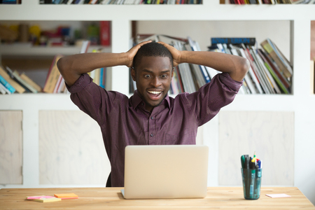 Excited African American worker looking eyes wide open winning lottery online, not believing his luck. Black associate happy with company growing rates. Concept of achievement, success and rewarding.