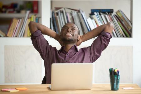 Tevreden zwarte werknemer ontspannen leunend in comfortabele stoel met handen boven het hoofd blij met voltooid werk, succesvol bedrijfsrapport en veelbelovende resultaten. Concept van belonen, rusten en winnen