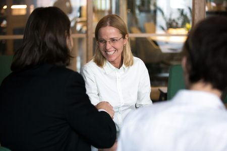 Smiling businesswoman shaking hand of businessman at group negotiations or job interview