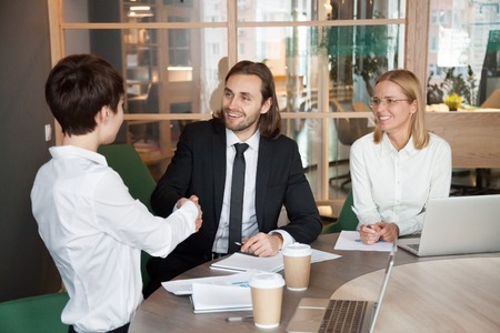 Smiling businessman and businesswoman shaking hands at team meeting or group negotiations