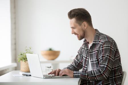 Smiling man freelancer working on laptop sitting at home office desk Stok Fotoğraf