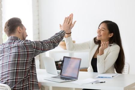 Junge asiatische und kaukasische Partner, die am Arbeitsplatz High Five vergeben, und verschiedene motivierte Kollegen feiern die Zielerreichung