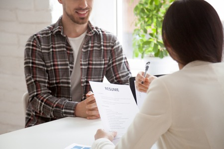 Hr manager reading smiling applicants resume at job interview, recruiter employer holding cv of confident vacancy candidate