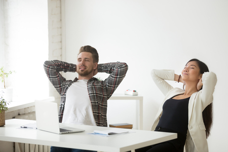Relaxed asian and caucasian office colleagues enjoy break at workplace breathing fresh air