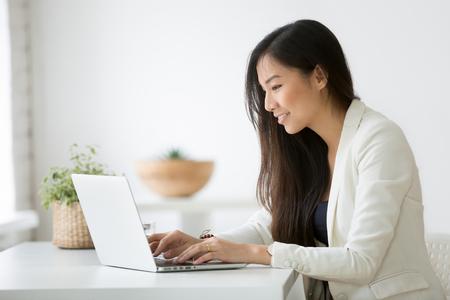 Glimlachende jonge Aziatische onderneemster die computer thuisbureauwerkplaats met behulp van