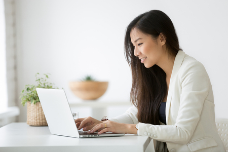 Uśmiechnięta młoda bizneswoman azjatyckiego przy użyciu komputera w domowym biurze pracy
