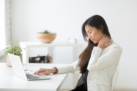 Young asian businesswoman touching massaging stiff neck to relieve pain in muscles after sedentary computer work in incorrect posture