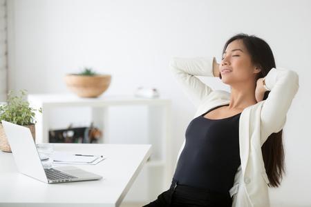 Entspannte glückliche asiatische Frau, die Pause am Arbeitsplatz genießt