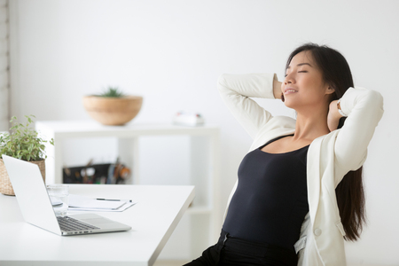 Relaxed happy asian woman enjoying break at workplace Stock Photo