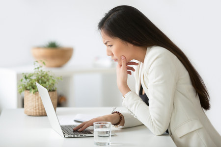 Puzzled confused asian woman thinking hard concerned about online problem solution looking at laptop screen