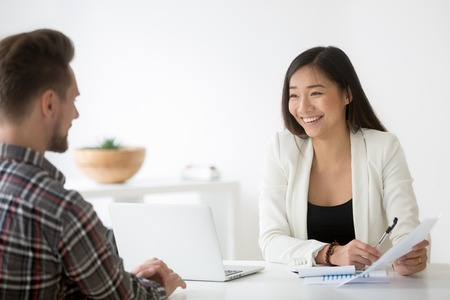 Vriendelijke Aziatische hr lachend lachen praten met kandidaat op sollicitatiegesprek Stockfoto