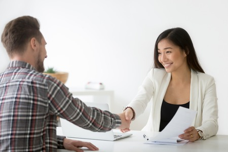 Smiling asian businesswoman handshaking businessman hiring candidate at job interview or signing contract making deal with customer