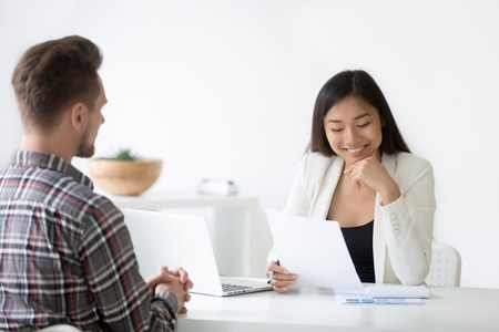 Good first impression at job interview concept, smiling asian woman hr reading resume of job seeker