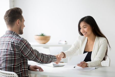 Happy asian businesswoman handshaking successful caucasian candidate holding employment agreement offering job contract Imagens