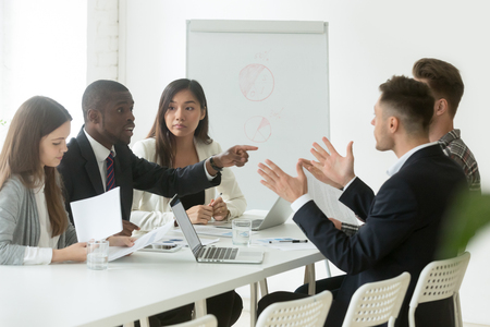 Diverse employees arguing during team meeting, african office worker disagreeing with caucasian colleague