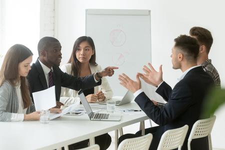 Verschiedene Mitarbeiter streiten sich während des Teammeetings, afrikanischer Büroangestellter widerspricht dem kaukasischen Kollegen