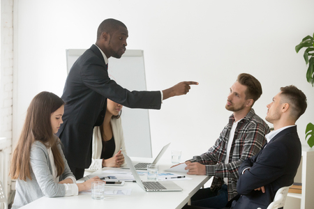 Angry rude african businessman pointing finger threatens caucasian colleague at team meeting