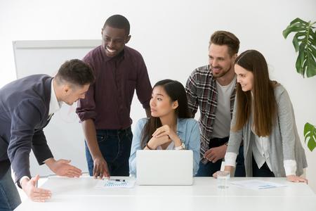 Kreative Geschäftsgruppe, die Diskussion am Bürotreffen hat und Fragen des asiatischen Teamleiters stellt Standard-Bild
