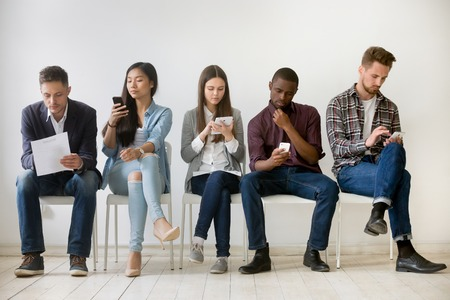 Diverse millennial unemployed people waiting in queue preparing for job interview