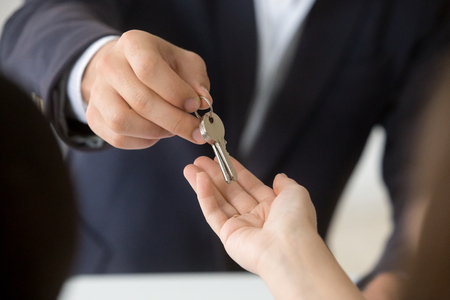 Female hand taking key from realtor buying renting new house, getting real estate ownership concept