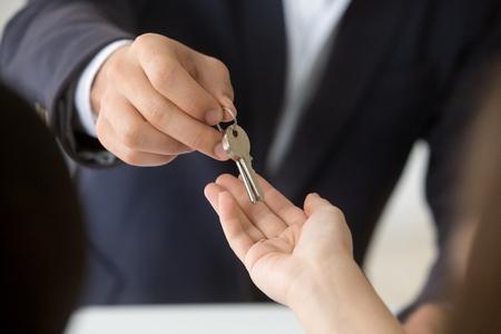 Vrouwelijke hand sleutel nemen van makelaar kopen, huren van nieuw huis, onroerend goed eigendom concept krijgen