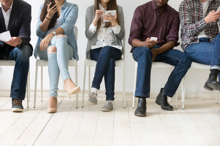 Diverse black and white people sitting in row using smartphones tablets, multiracial men and women waiting for job interview
