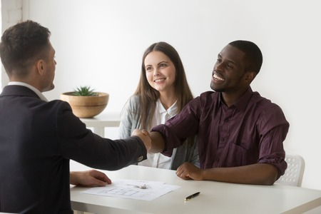 Happy satisfied interracial couple and realtor shaking hands making real estate deal