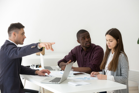 Rude multiracial businessmen humiliating, offending or firing upset frustrated businesswoman colleague telling to leave group meeting Stock Photo