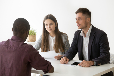 Serious thoughtful caucasian hr managers listen to african applicant at job interview