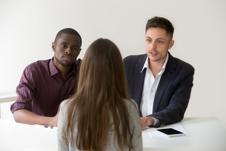 Serious african and caucasian hr managers interviewing female job applicant