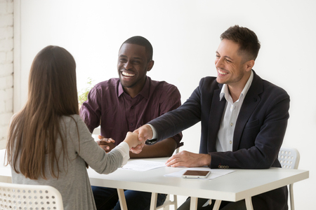 Smiling multiracial hr handshaking female applicant won job interview