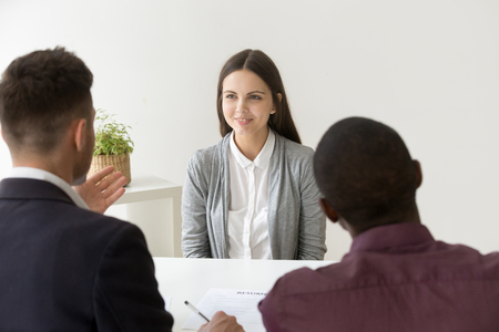 Confident female applicant smiling at job interview with diverse hr managers