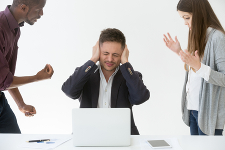 Tired from work or noise businessman closing ears with hands not to hear claims of annoying complaining clients