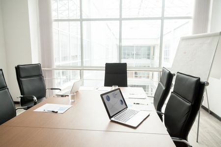 Modern office boardroom interior with laptops documents on conference table and big window Foto de archivo
