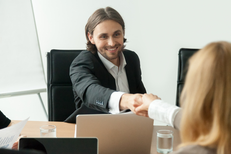 Smiling businessman in suit handshaking greeting businesswoman at group negotiation
