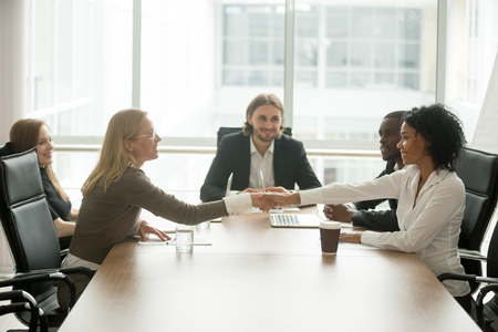 Diverse smiling businesswomen shaking hands greeting at multiracial group meeting Фото со стока - 101472992