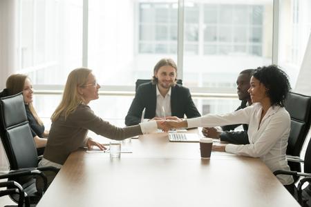 Diverse smiling businesswomen shaking hands greeting at multiracial group meeting