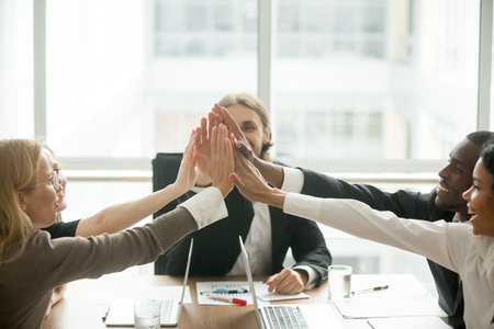 Excited happy multiracial business team giving high five at office meeting motivated by victory