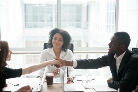 Sorridente imprenditore africano handshake saluto imprenditrice indoeuropea al gruppo di negoziazione di riunione