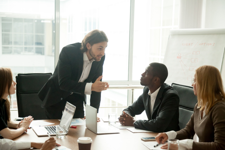 Angry mean boss scolding incompetent employee for bad work results at diverse group meeting